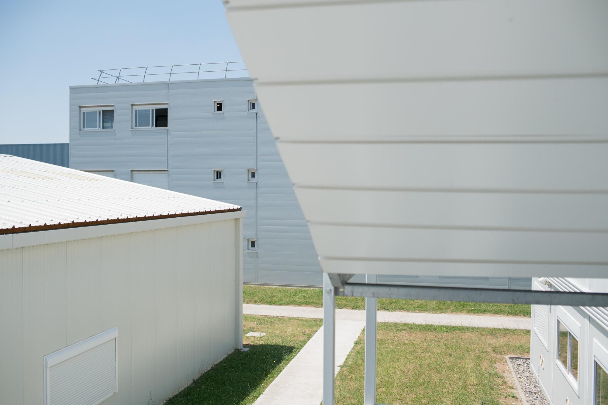 Vue extérieure d'un enchevêtrement de préfabriqués blancs, lieu de travail de Christophe