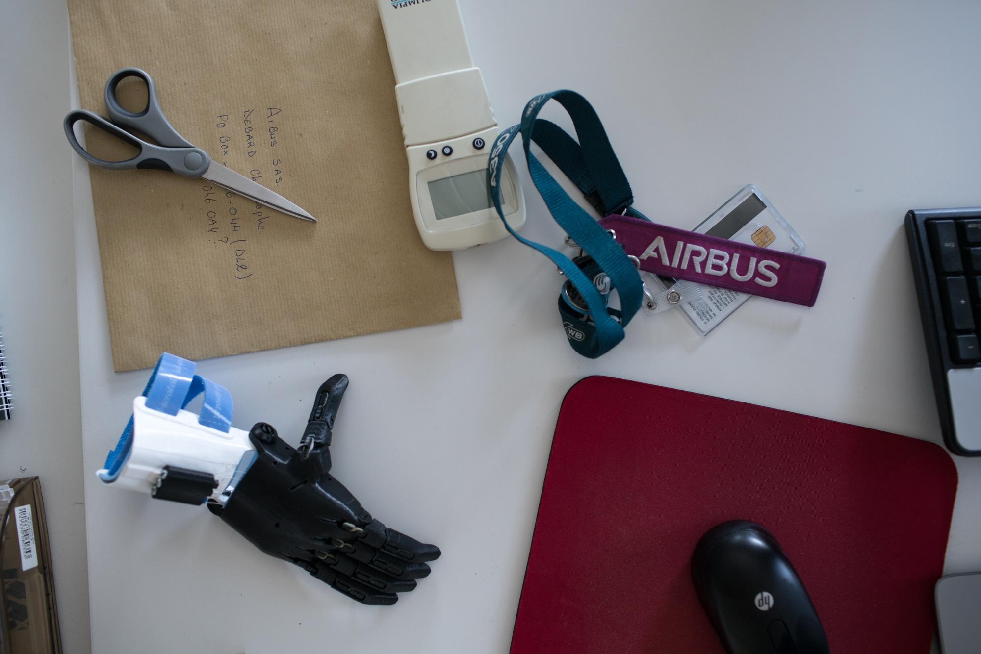 Sur un bureau sont éparpillés un trousseau de clés, une souris d'ordinateur, une paire de ciseaux, un instrument éléctronique et une prothèse de main imprimée en 3D