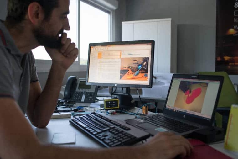 Christophe travaille à son bureau devant deux ordinateurs montrant des prototypes de prothèses de jambes