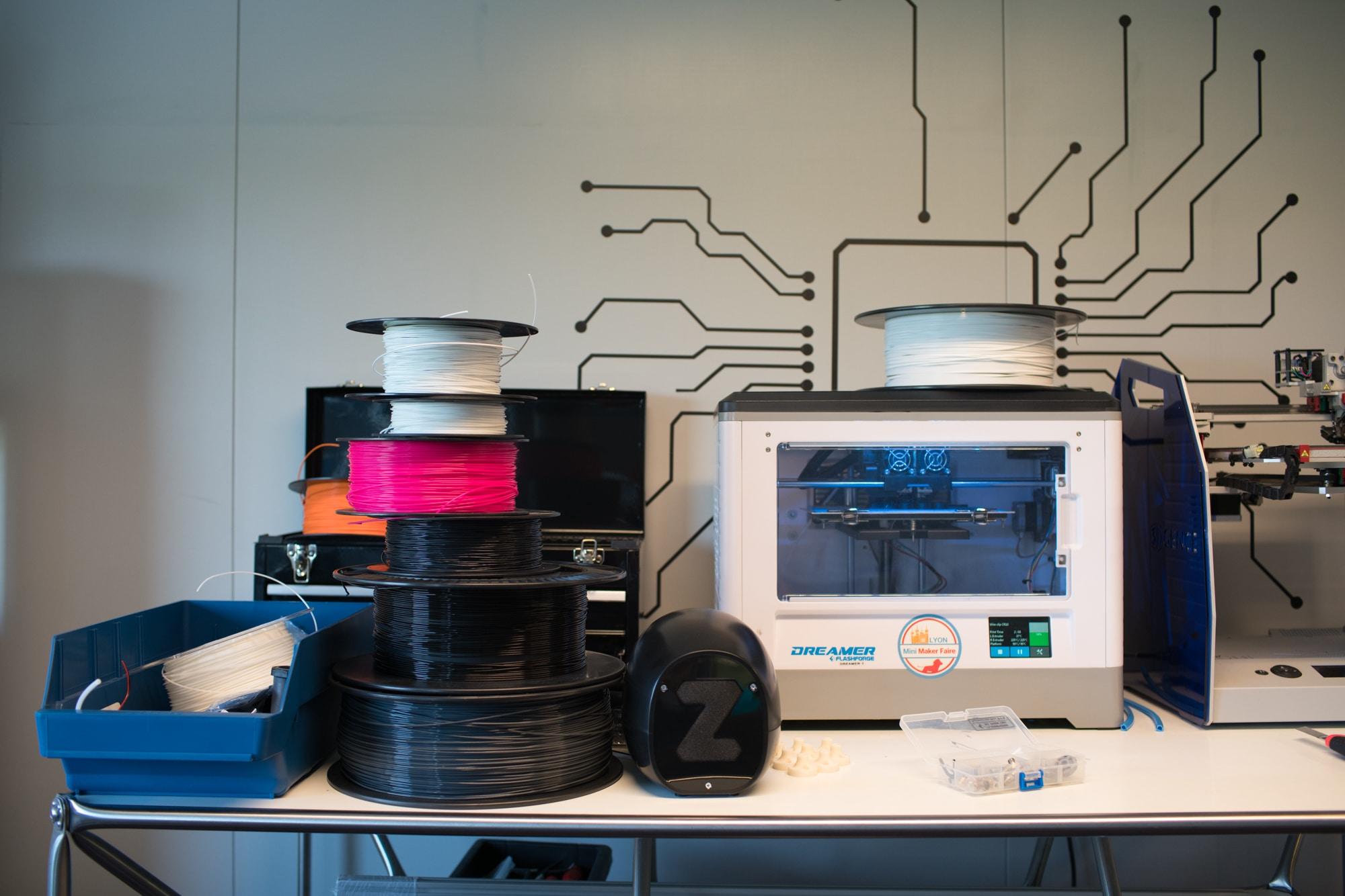 Une imprimante 3D sur un bureau, entourée de bobines de matière première de différentes couleurs