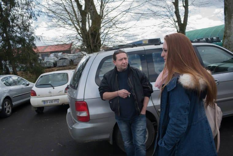 Damien Nowak, accoudé à une voiture, discute avec sa cliente
