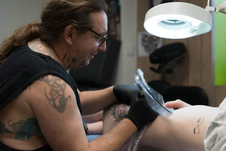Penché sur son sujet, Damien continue de tatouer en souriant