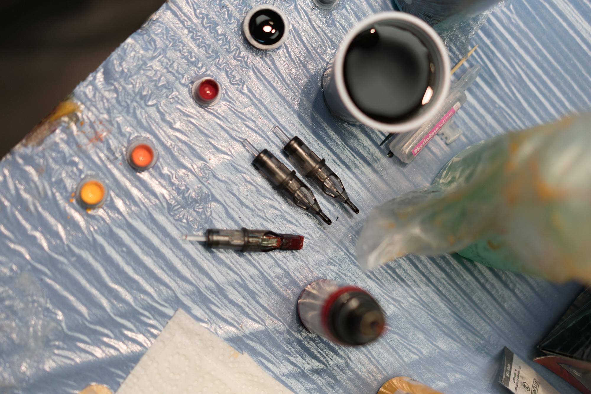 Un aperçu de la table de Damien, présentant les différentes aiguilles et encres employées