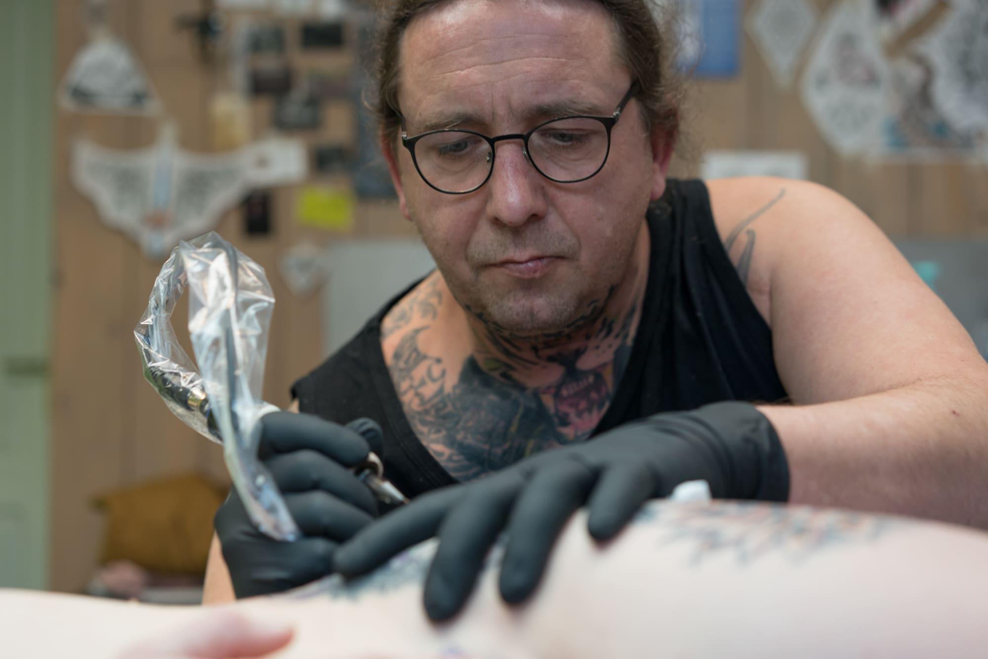 Vu de face, Damien est concentré sur le tatouage en cours, aiguille à la main