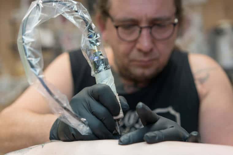 Au premier plan les mains de Damien tatouent la hanche. Au second plan, Damien, concentré