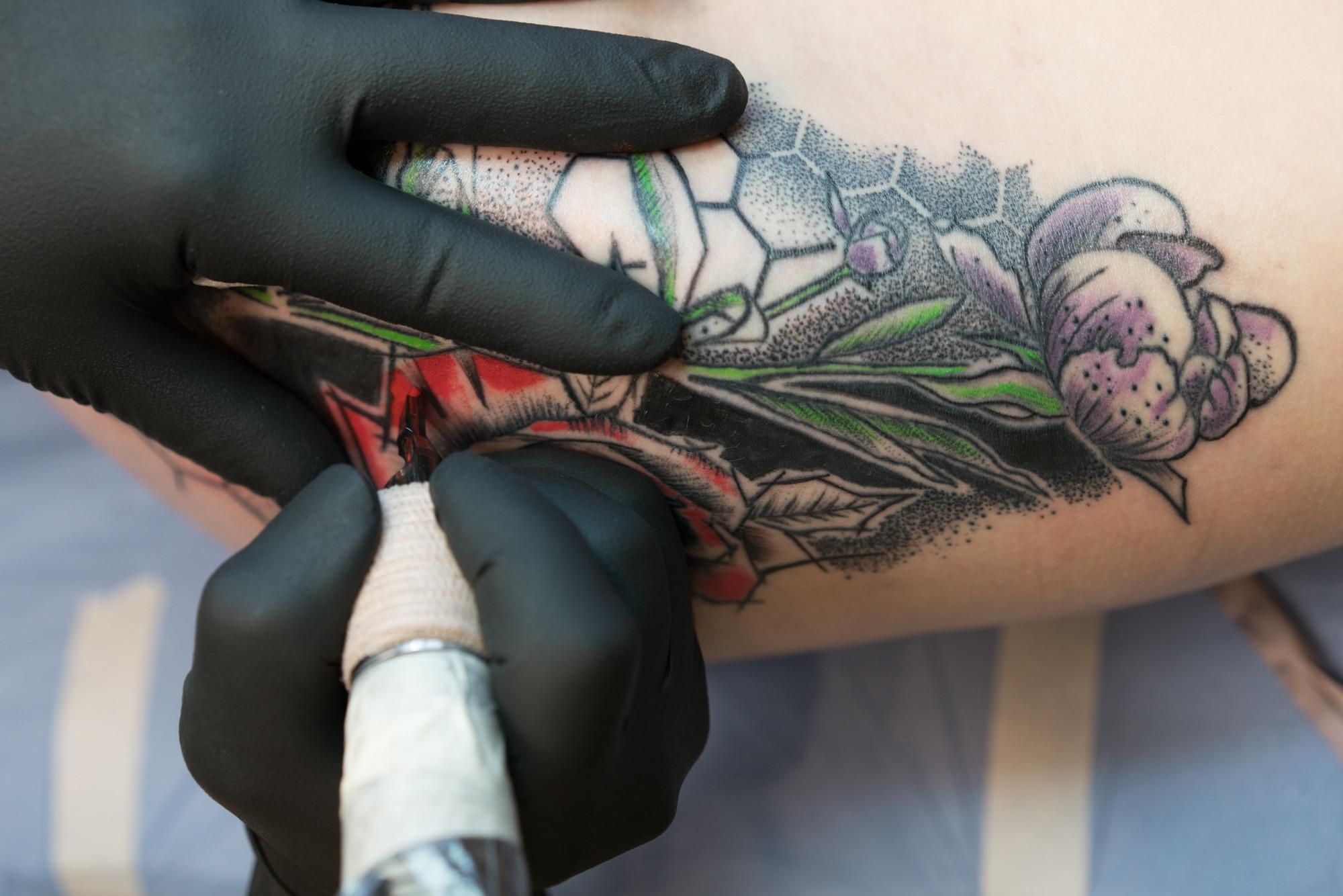 Les mains de Damien s'emploient à remplir une section du tatouage sur la hanche. On peut distinguer des fleurs stylisées