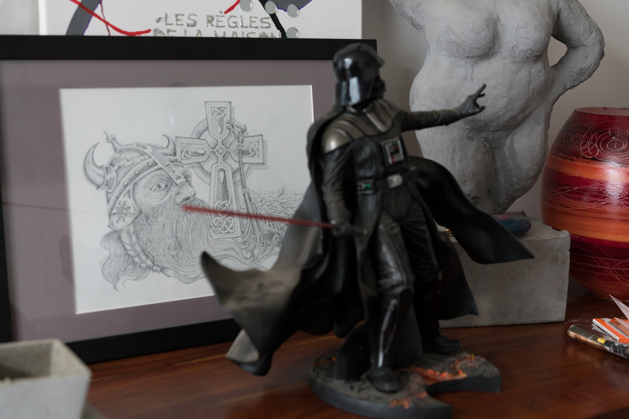 Sur une table sont disposés une figurine de Darth Vader, une sculpture de silhouette féminine, et un dessin encadré représentant un homme barbu à casque viking à côté d'une croix celte