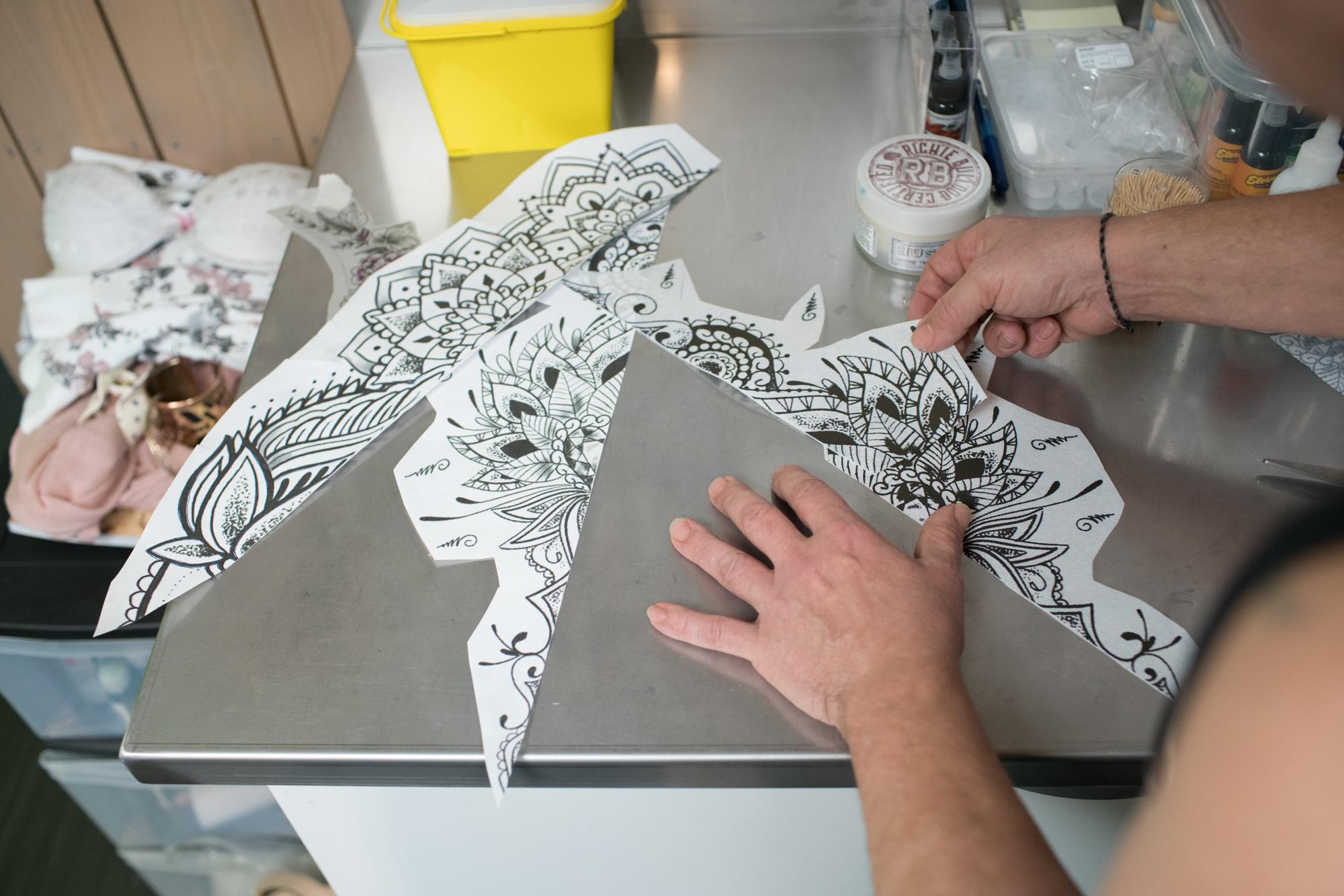 Les mains de Damien positionnent les dessins préparatoires du tatouage