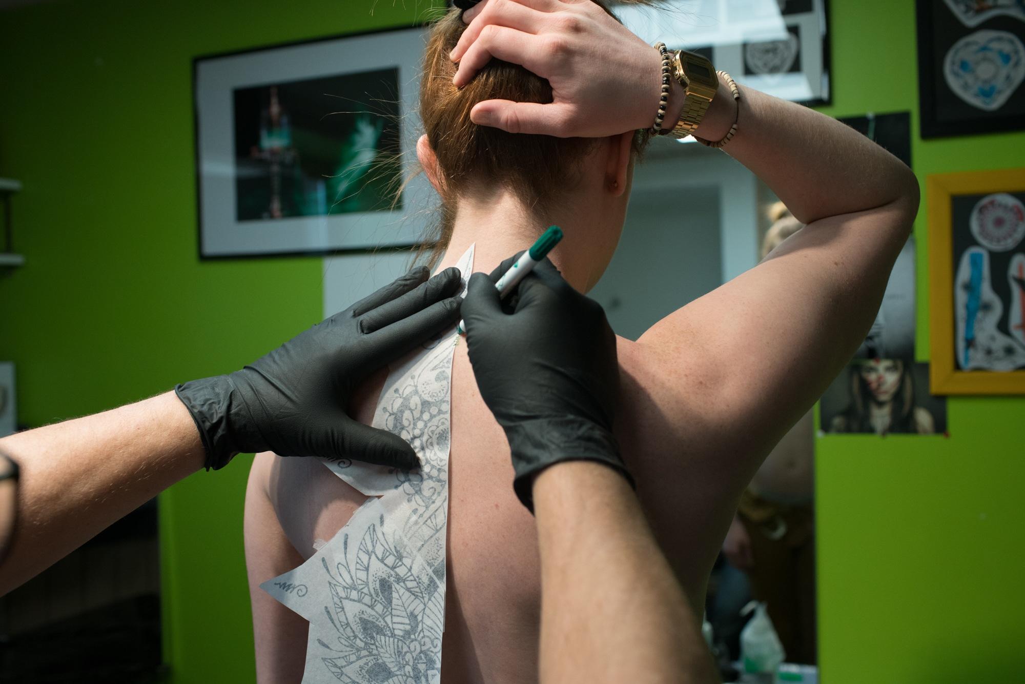 Damien retrace le tatouage sur le dos de sa cliente en se servant du dessin préparatoire