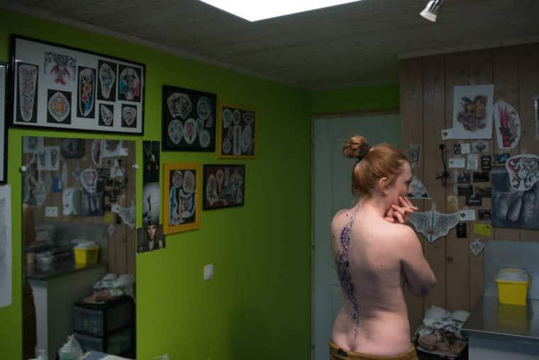 Au sein de l'atelier de Damien, tapissé de dessins, se tient sa cliente de dos, arborant le dessin de son futur tatouage