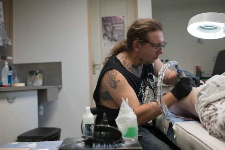 Damien, assis, tatoue la hanche de sa cliente