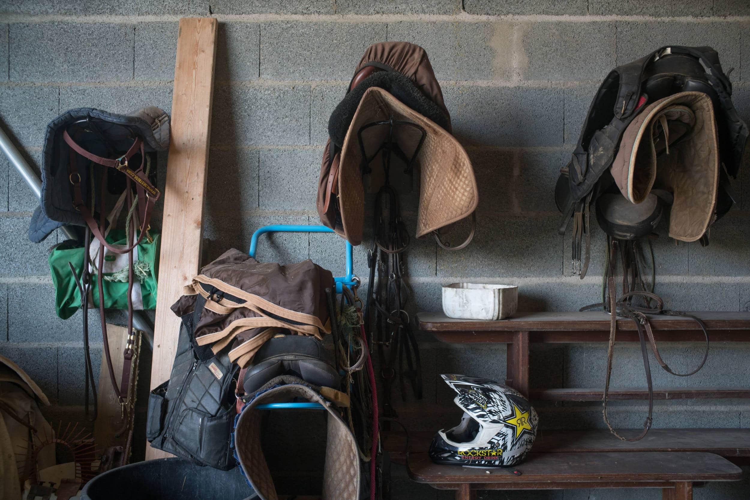 Des selles et divers accessoires sont suspendus au mur et répartis sur le sol. Un casque de moto-cross est également posé sur un banc.