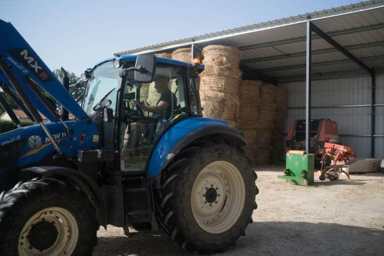 David consduit un tracteur bleu devant une grange dans laquelle sont entreposées des meules de foin.