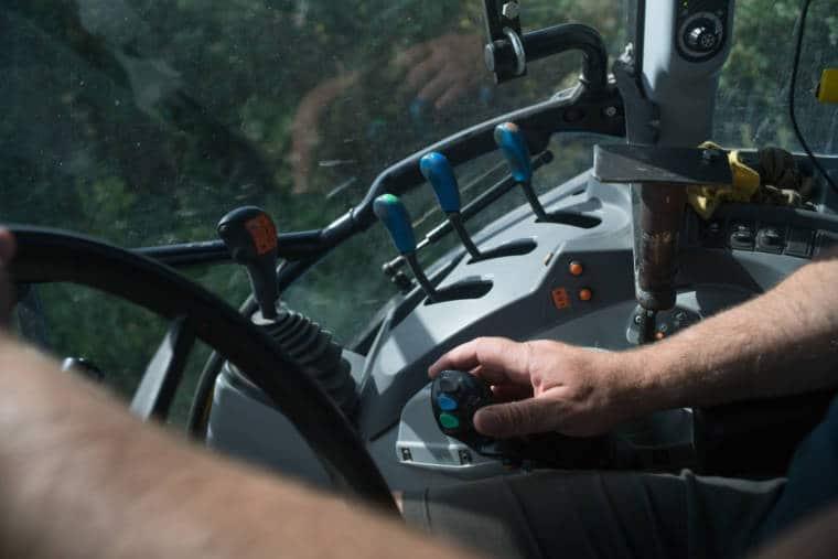 Vue de l'intérieur du tracteur. La main de David est posée sur une commande présentant de multiples boutons.
