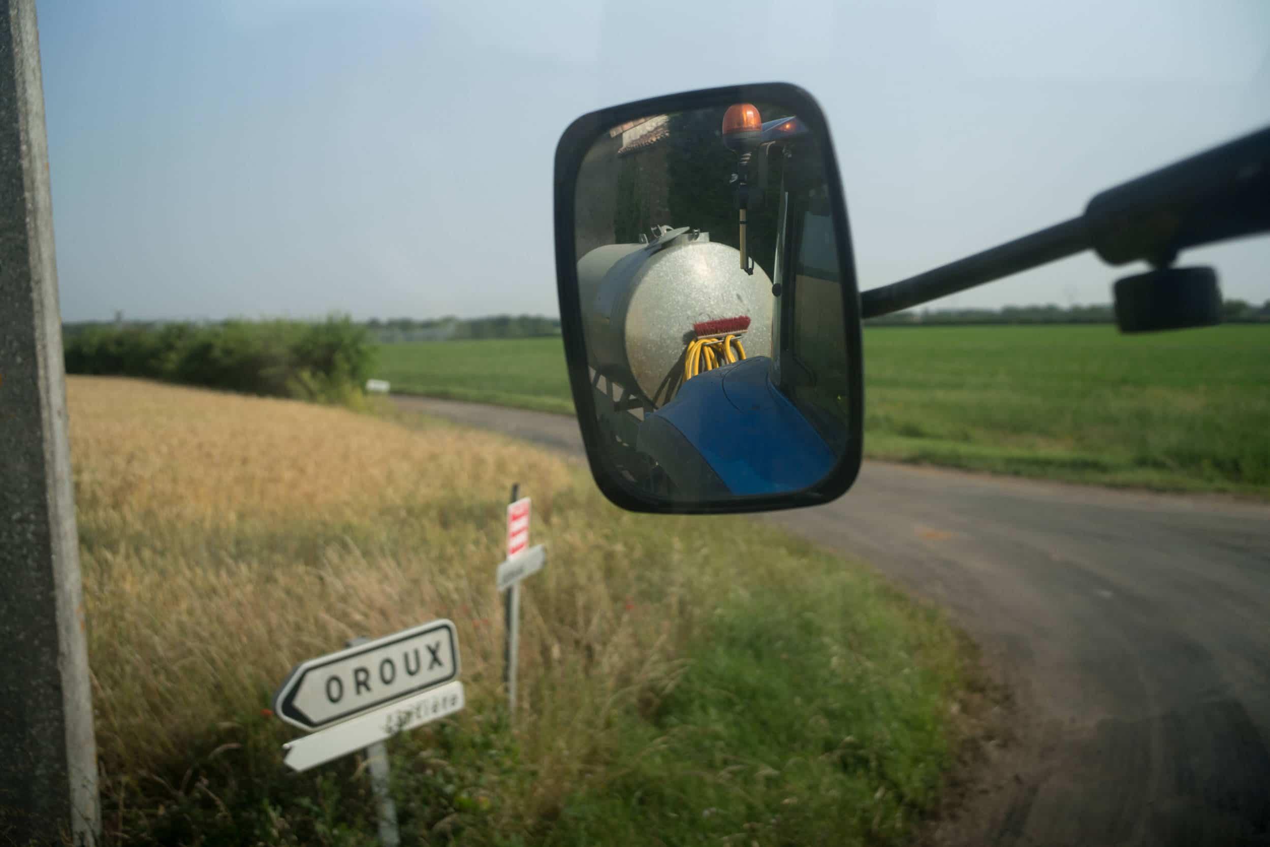 """Au premier plan, le rétroviseur du tracteur montre la citerne qu'il remorque. Au second plan s'étendent les champs et des panneaux d'indication portant la mention """"Oroux""""."""