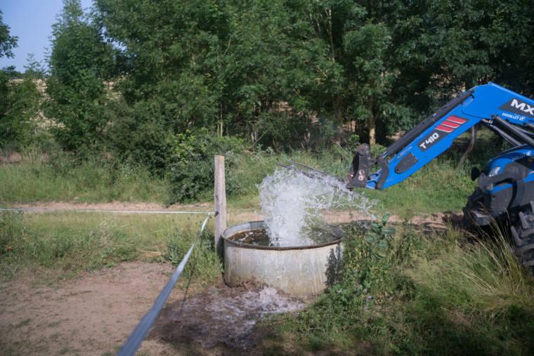 Le bras articulé du tracteur sort d'un grand réservoir d'eau, éclaboussant les herbes alentour.