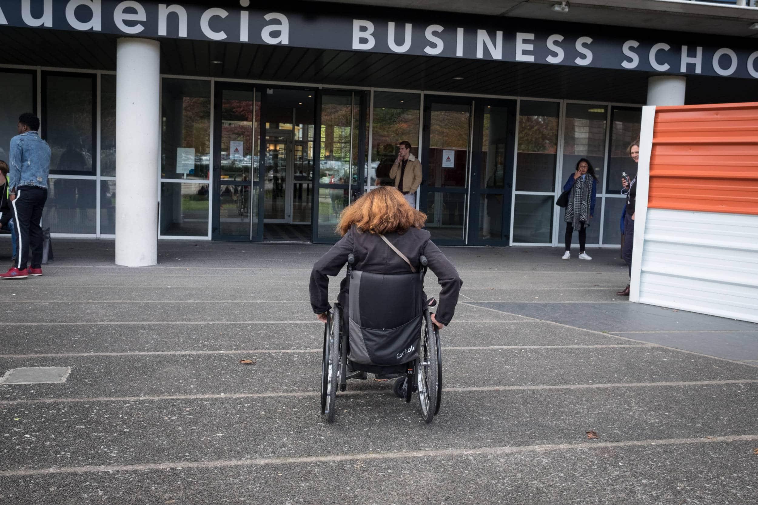 Delphine, de dos, se déplace en fauteuil roulant.