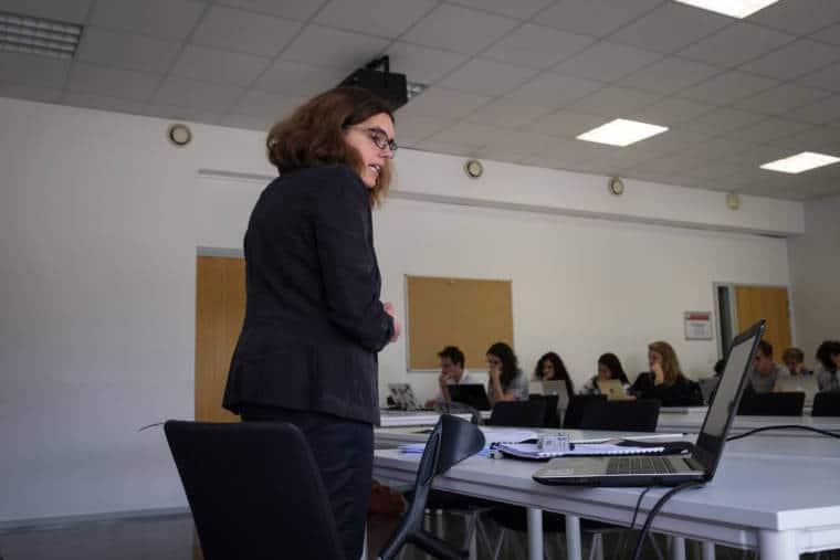 Delphine s'adresse à sa classe en consultant son ordinateur