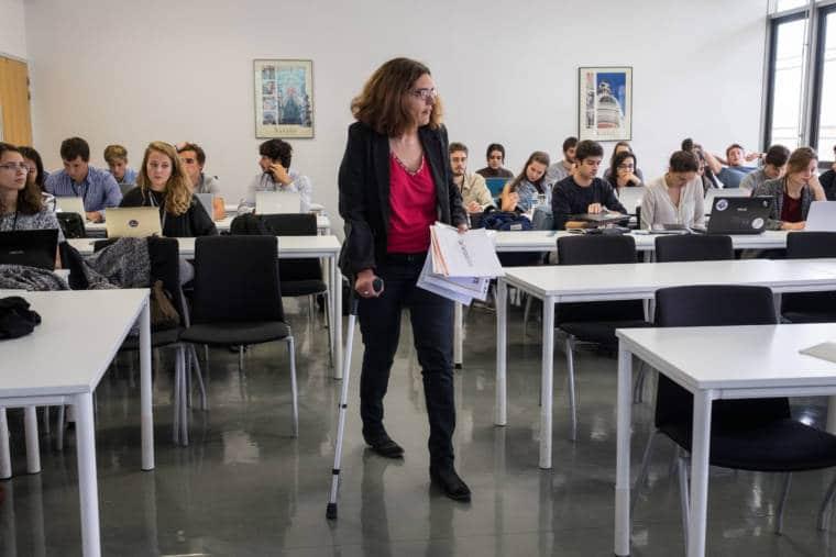 Delphine se déplace dans sa classe à l'aide d'une béquille, des documents à la main