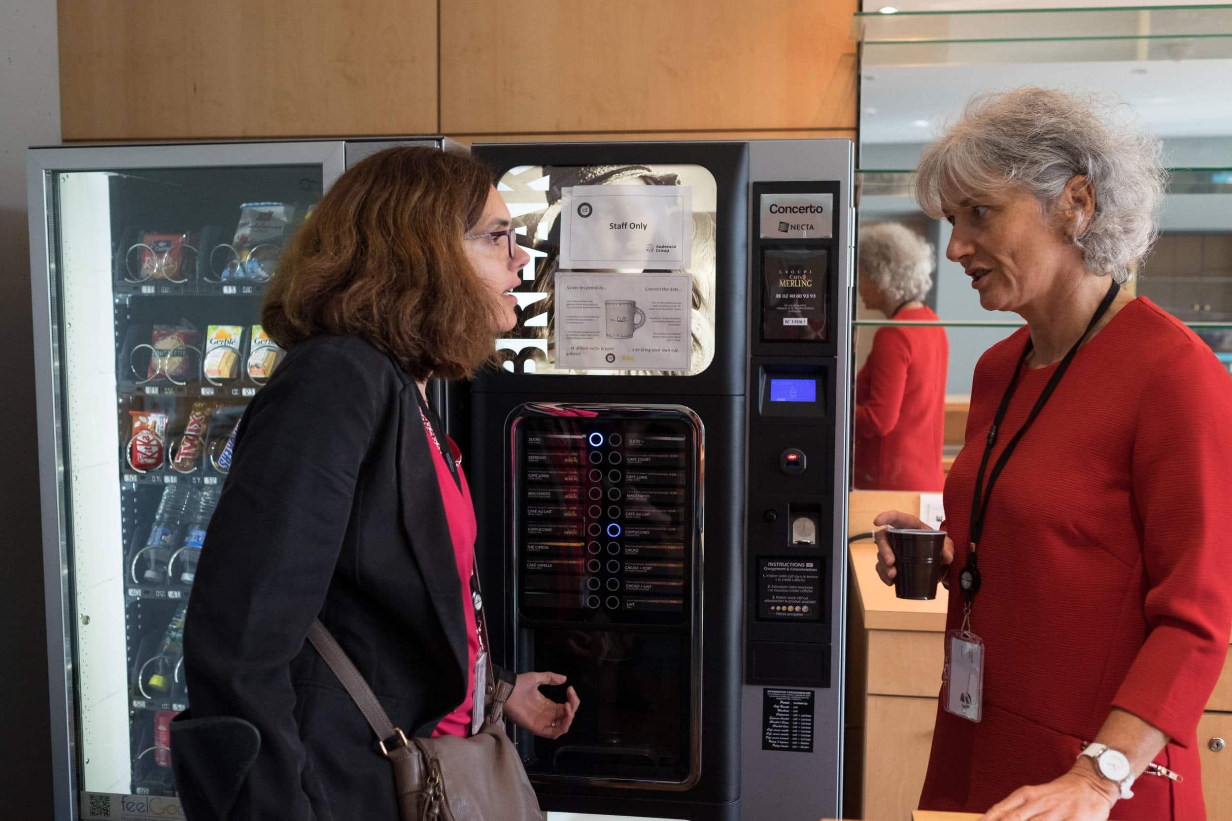Delphine discute avec une collègue devant une machine à café
