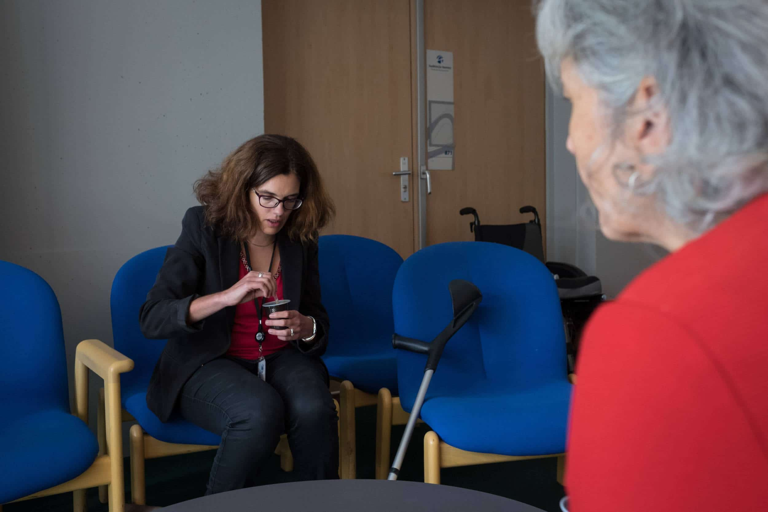 Delphine, assise sur une chaise, remue son café en discutant avec une collègue de travail