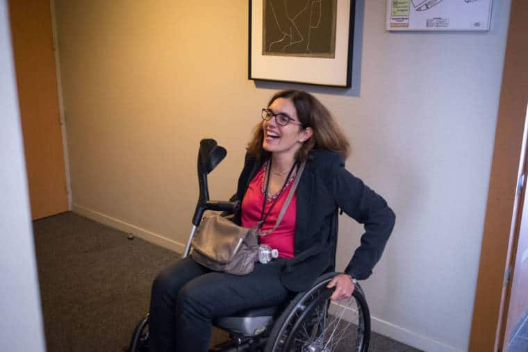 Delphine, riant, sur son fauteuil roulant
