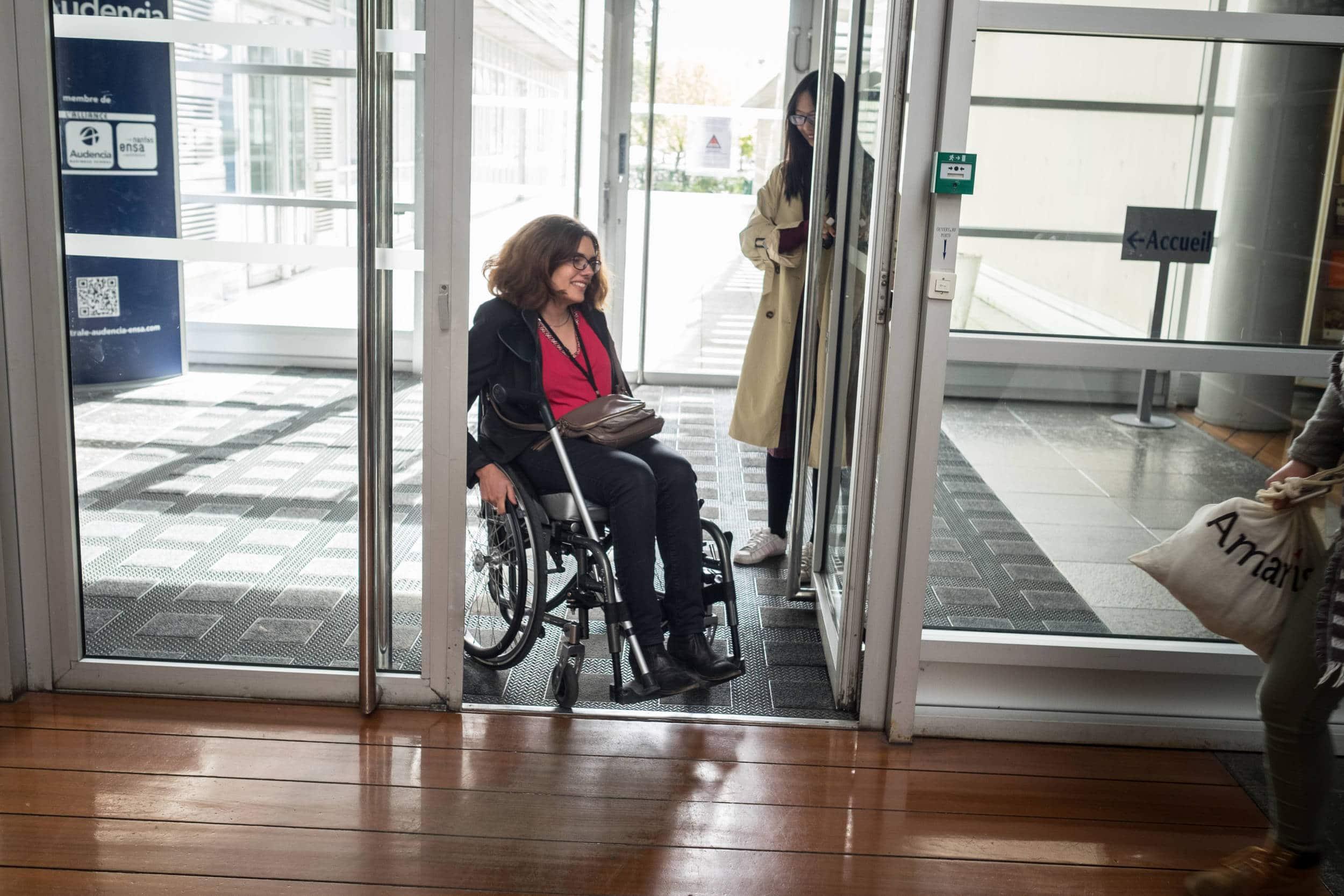 Delphine, souriante, passe une porte en fauteuil roulant.