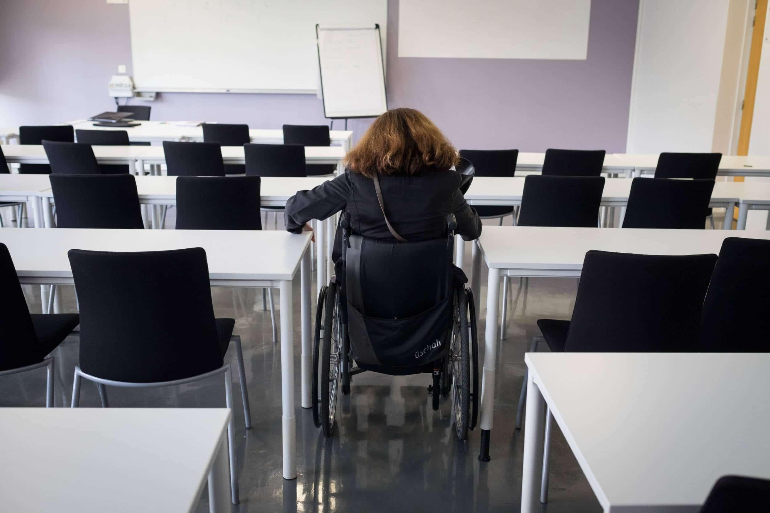 Delphine en fauteuil roulant, de dos, dans une classe vide.