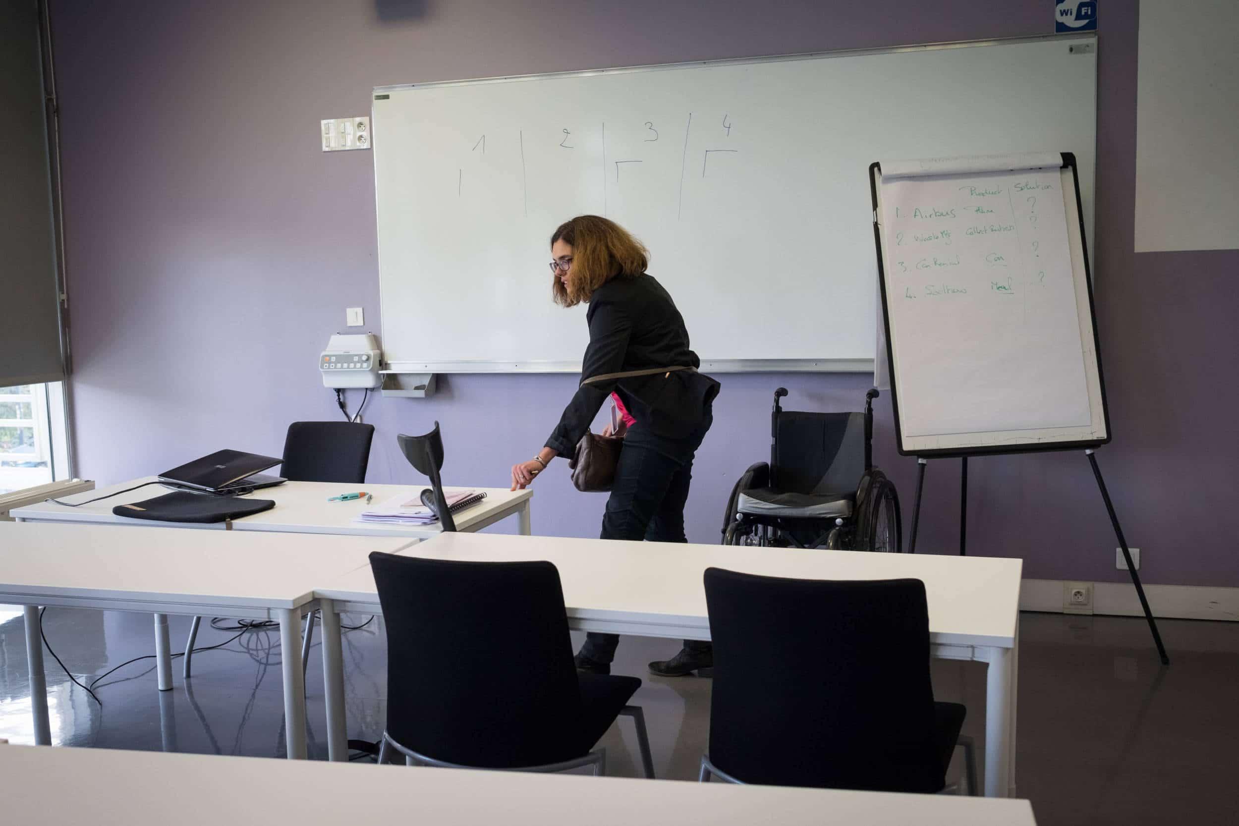 Delphine, dans la classe vide, se lève de son fauteuil et s'appuie sur son bureau.