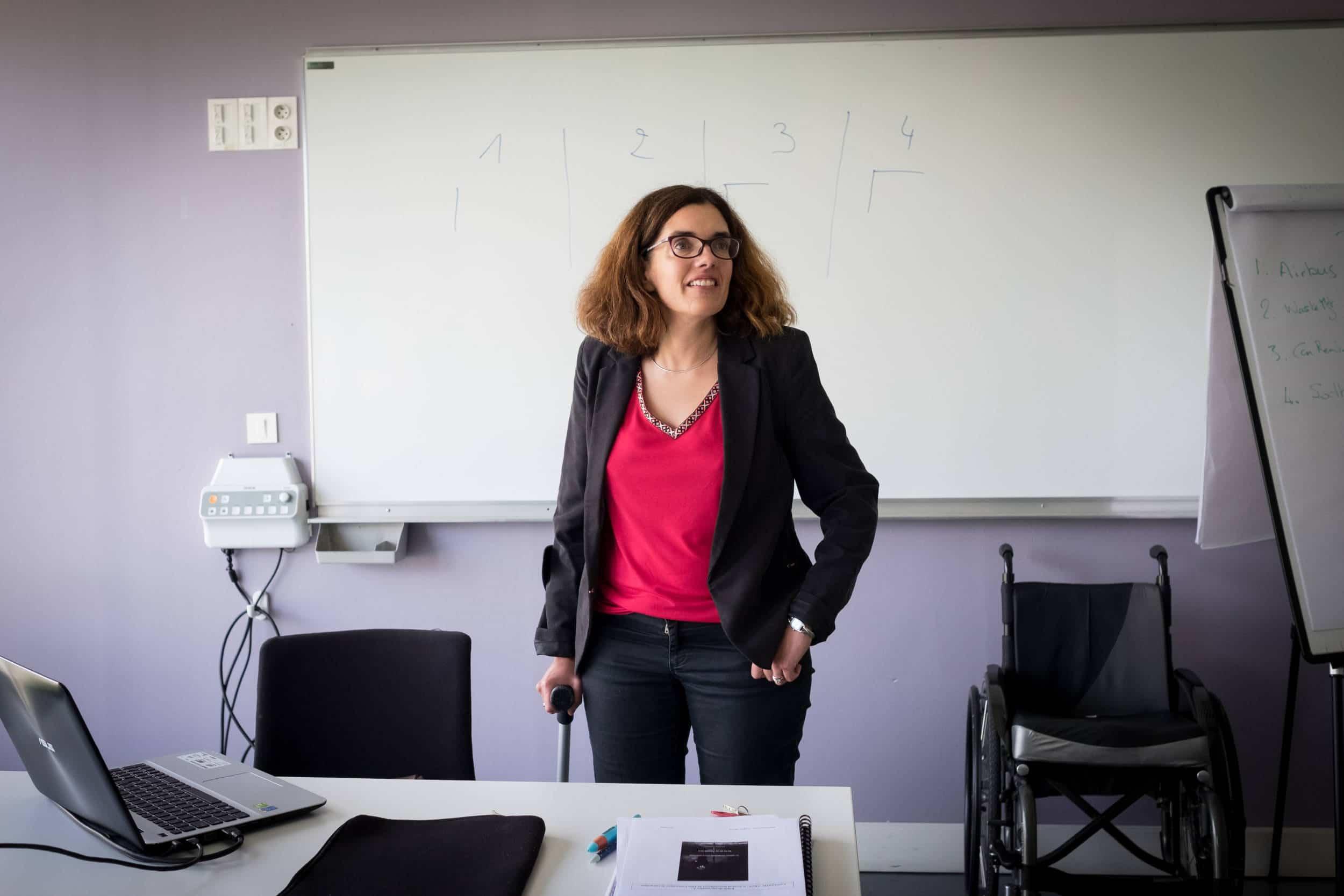 Delphine, appuyée sur une canne et souriante, est derrière son bureau pendant le cours.