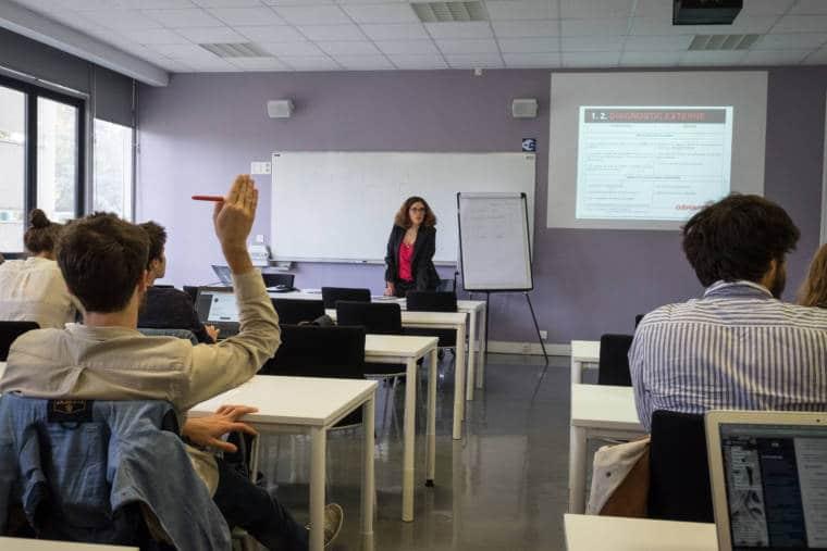 Un élève lève la main au premier plan tandis que Delphine donne son cours.