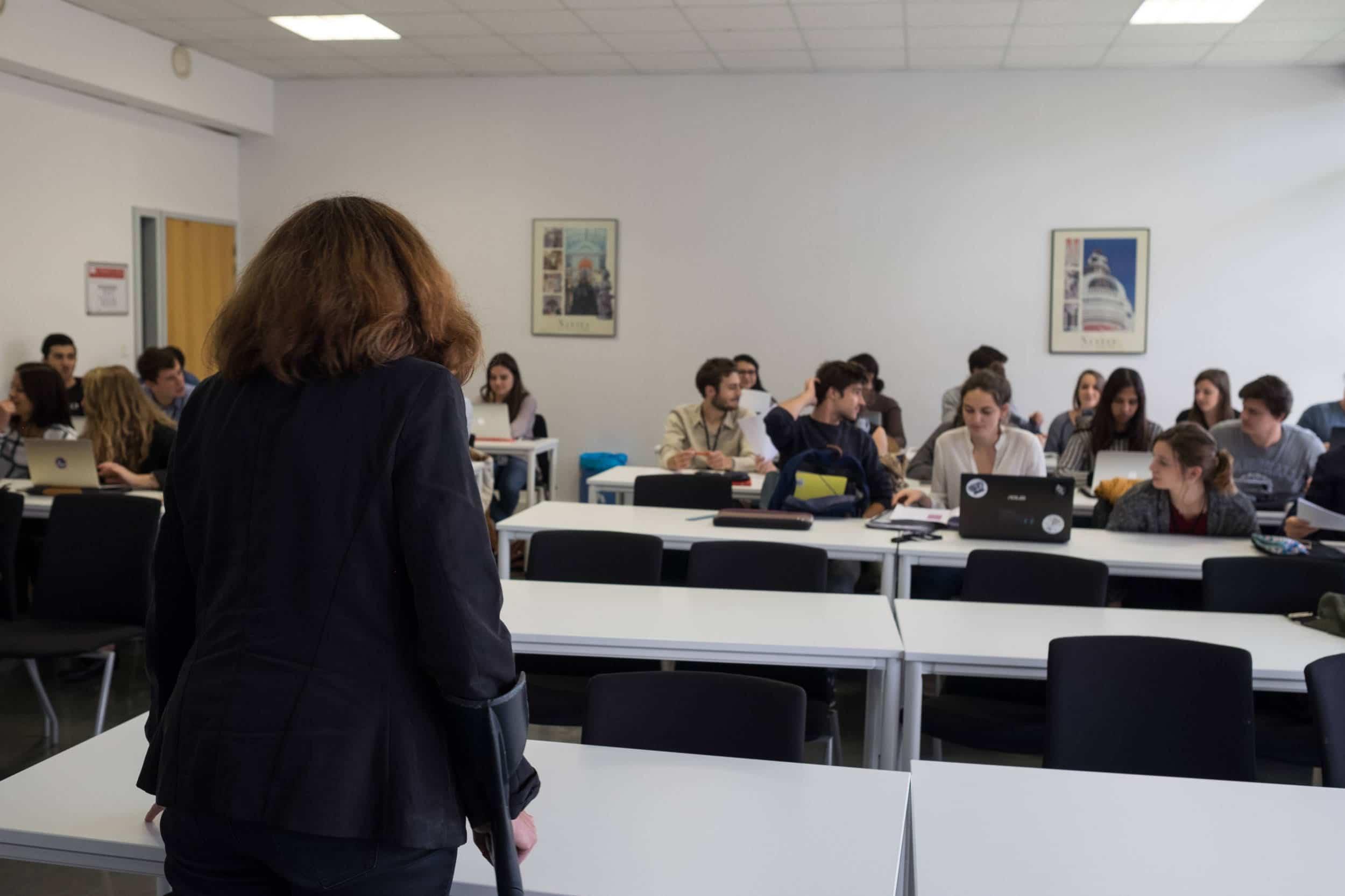 Delphine, vue de dos, donne un cours à ses élèves regroupés en face