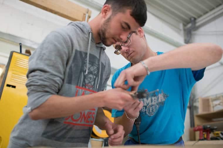 Edouard Nicaise manipule un outil avec un collaborateur