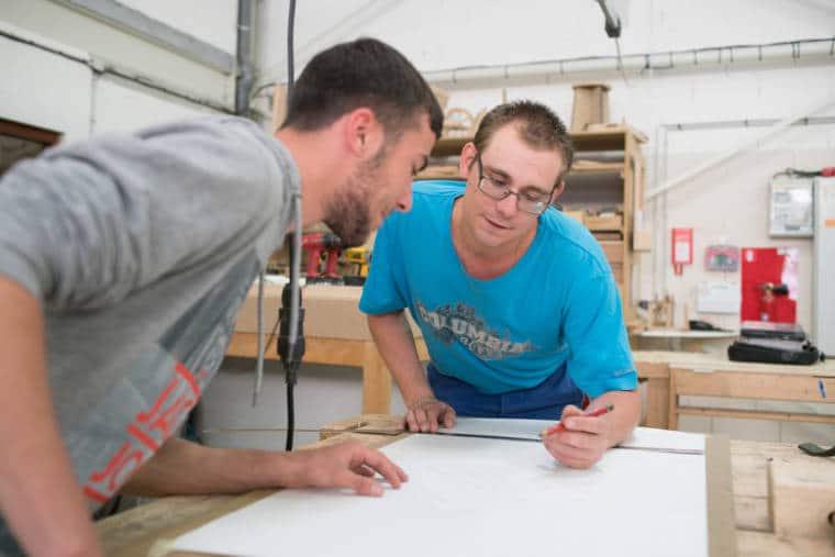 Edouard, un crayon à la main, est penché sur un plan d'architecture