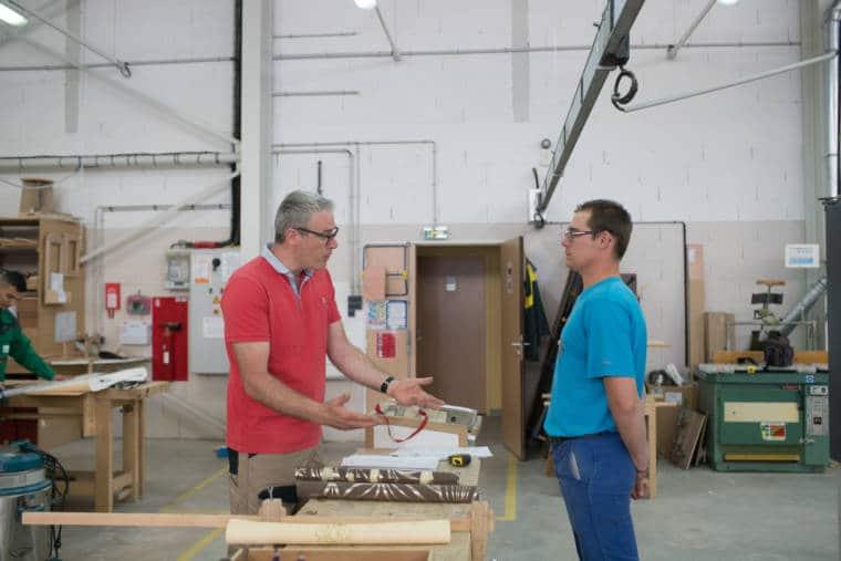 Au sein d'un atelier, Edouard écoute un collaborateur, les deux mains jointes dans le dos
