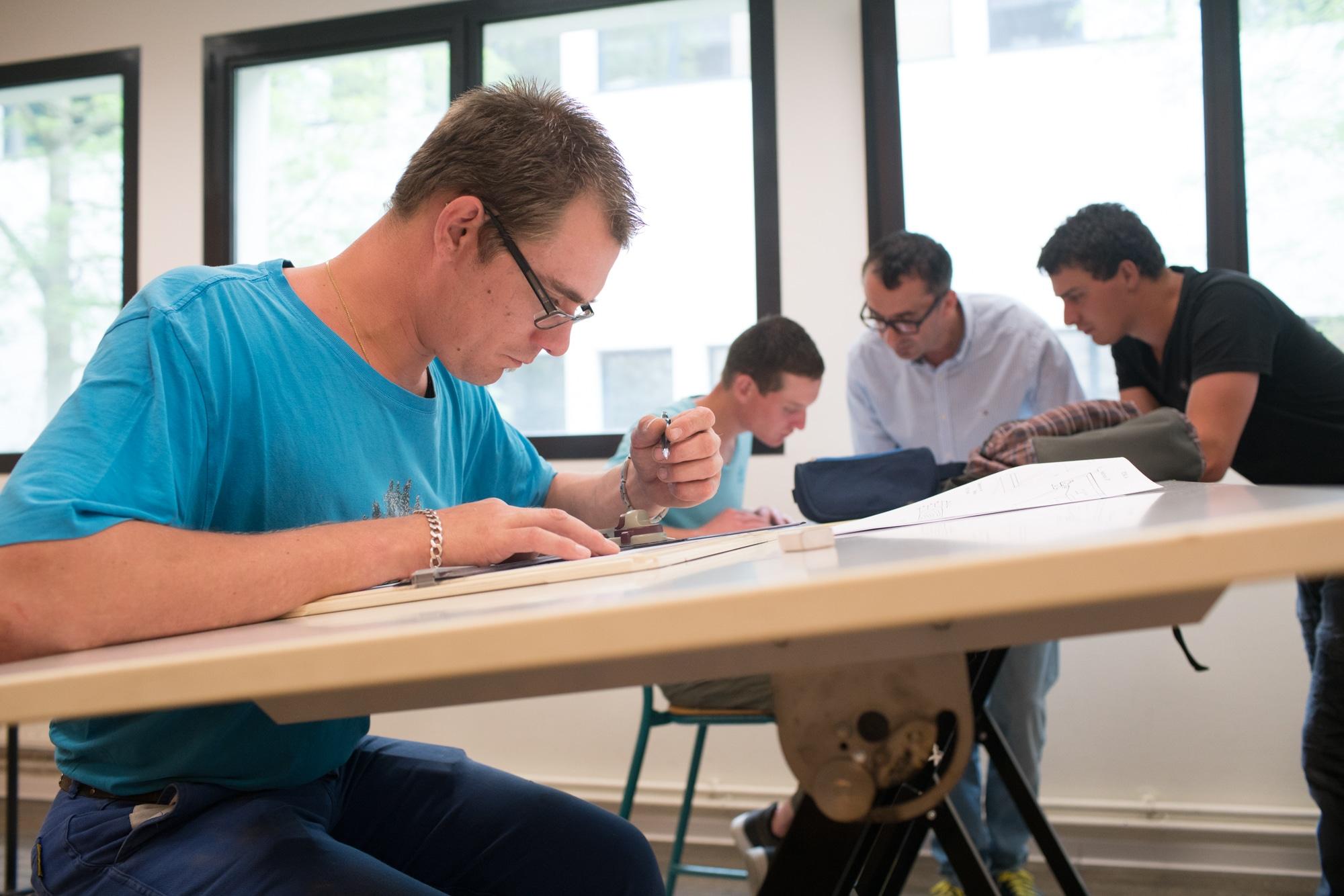 Assis et penché sur une table inclinée, Edouard réalise un plan avec un porte mine et divers outils de mesure