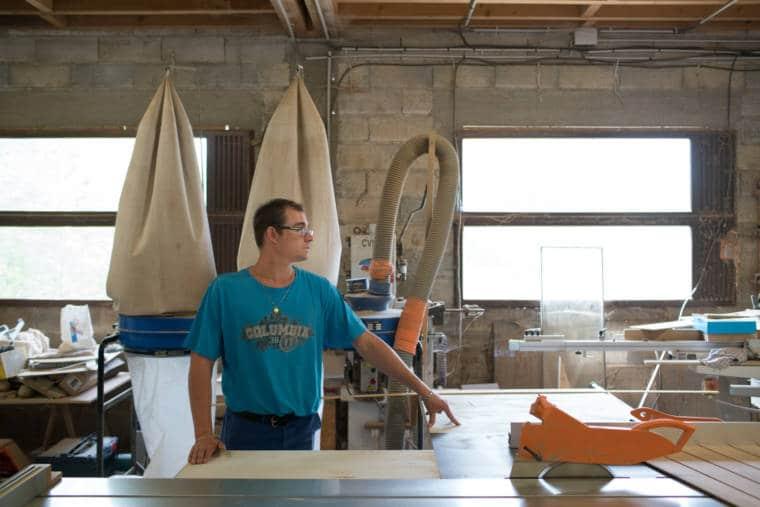 Debout dans un atelier, une main posée sur une table, Edouard observe un coin de la pièce