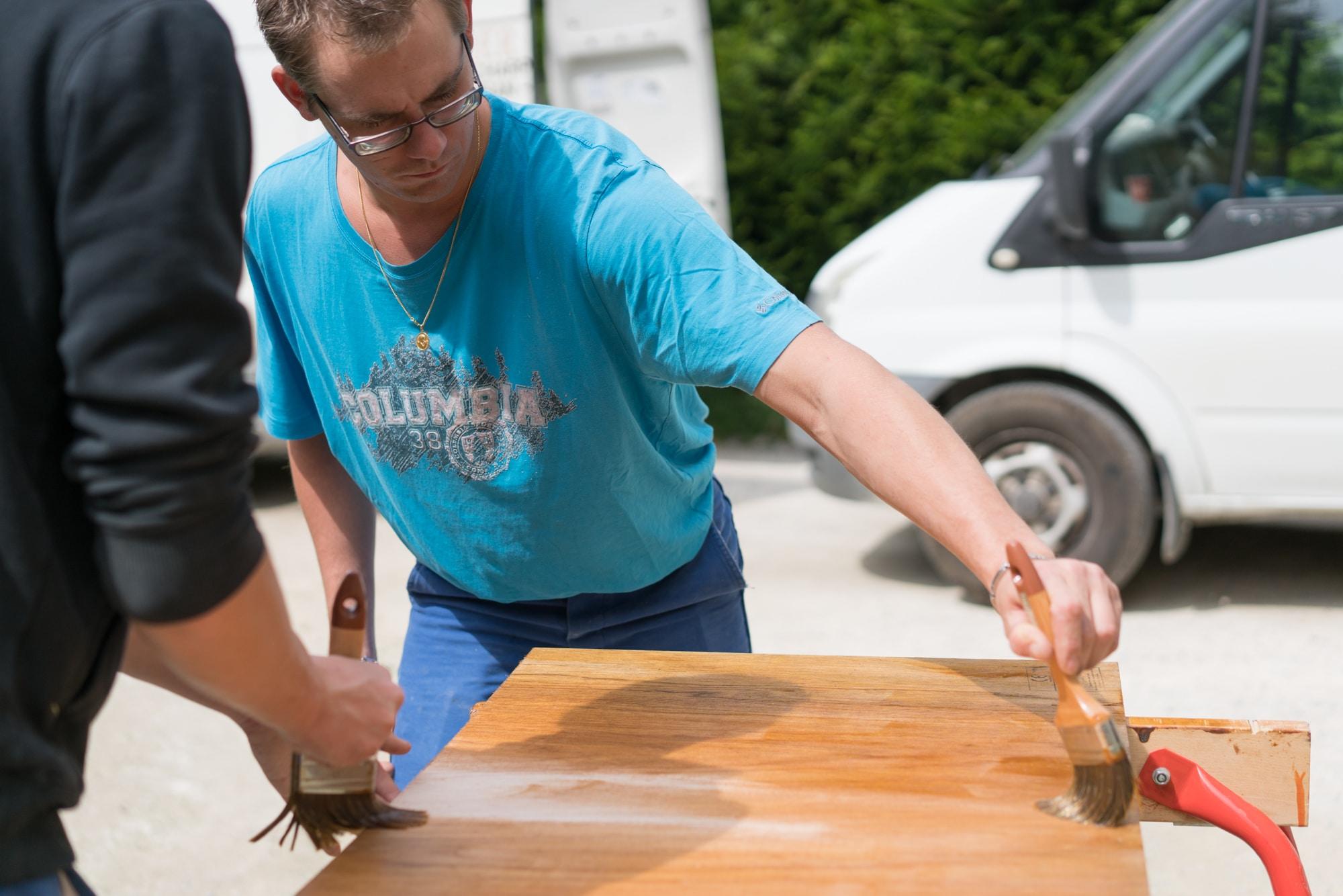 Edouard, à l'extérieur, passe une couche de vernis sur une découpe de bois à l'aide d'un pinceau