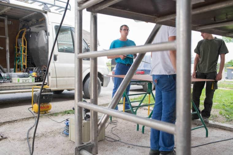 Edouard, portant une planche à l'extérieur entre un camion et un échafaudage, discute avec un collaborateur.
