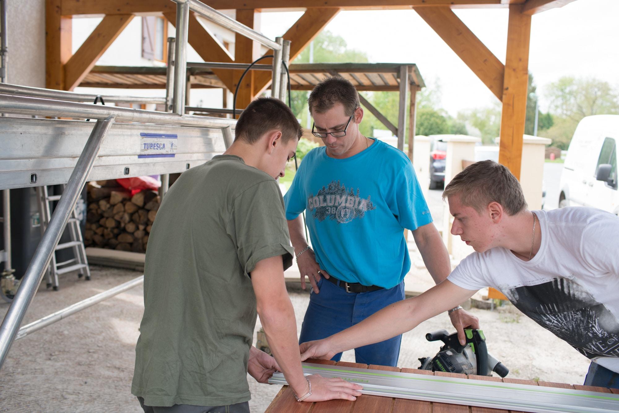 Edouard et deux collaborateurs travaillent autour d'une découpe de bois avec une règle en métal