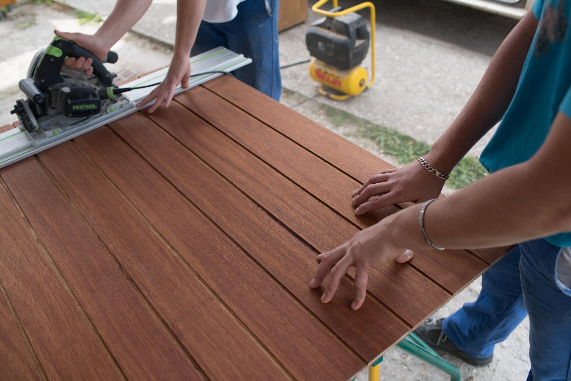 Les mains d'Edouard stabilisent une planche alors qu'un collaborateur la coupe à l'aide d'une scie électrique