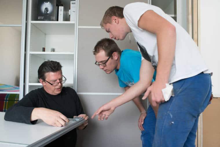 Edouard observe un collaborateur qui visse une pièce sur un pan d'armoire