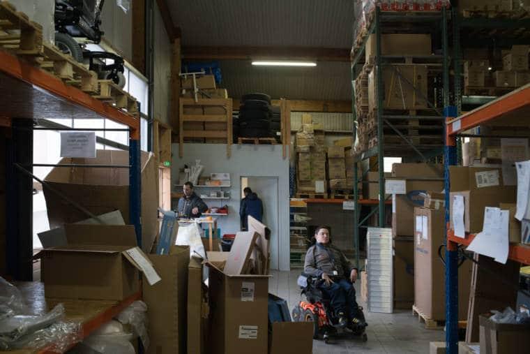 Un plan large présentant Edouard dans un grand entrepôt contenant palettes et cartons