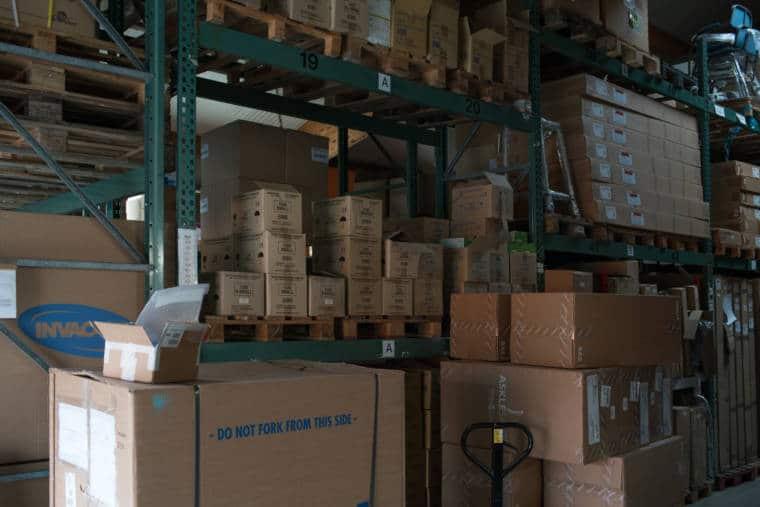 Un coin de l'entrepôt où s'empilent des cartons sur de grandes étagères