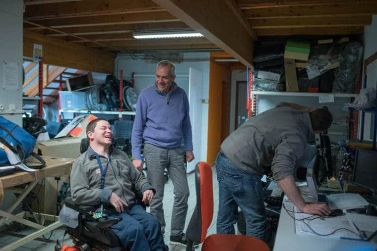 Edouard, riant, entouré de son employeur et d'un collègue de travail