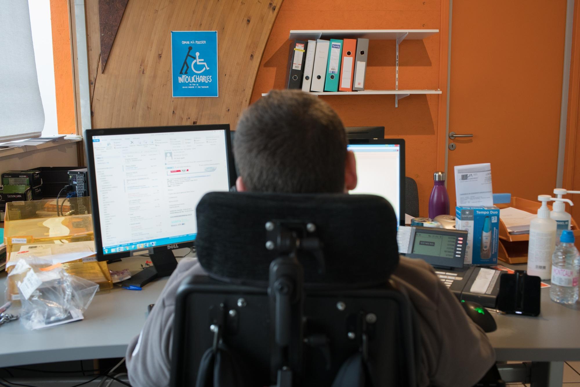 Edouard, vu de dos, travaille devant ses deux écrans d'ordinateur