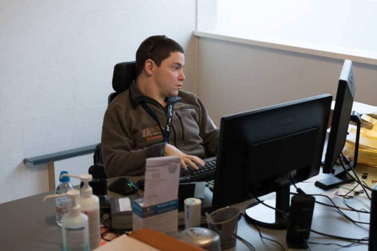 Vue d'ensemble présentant Edouard devant son ordinateur