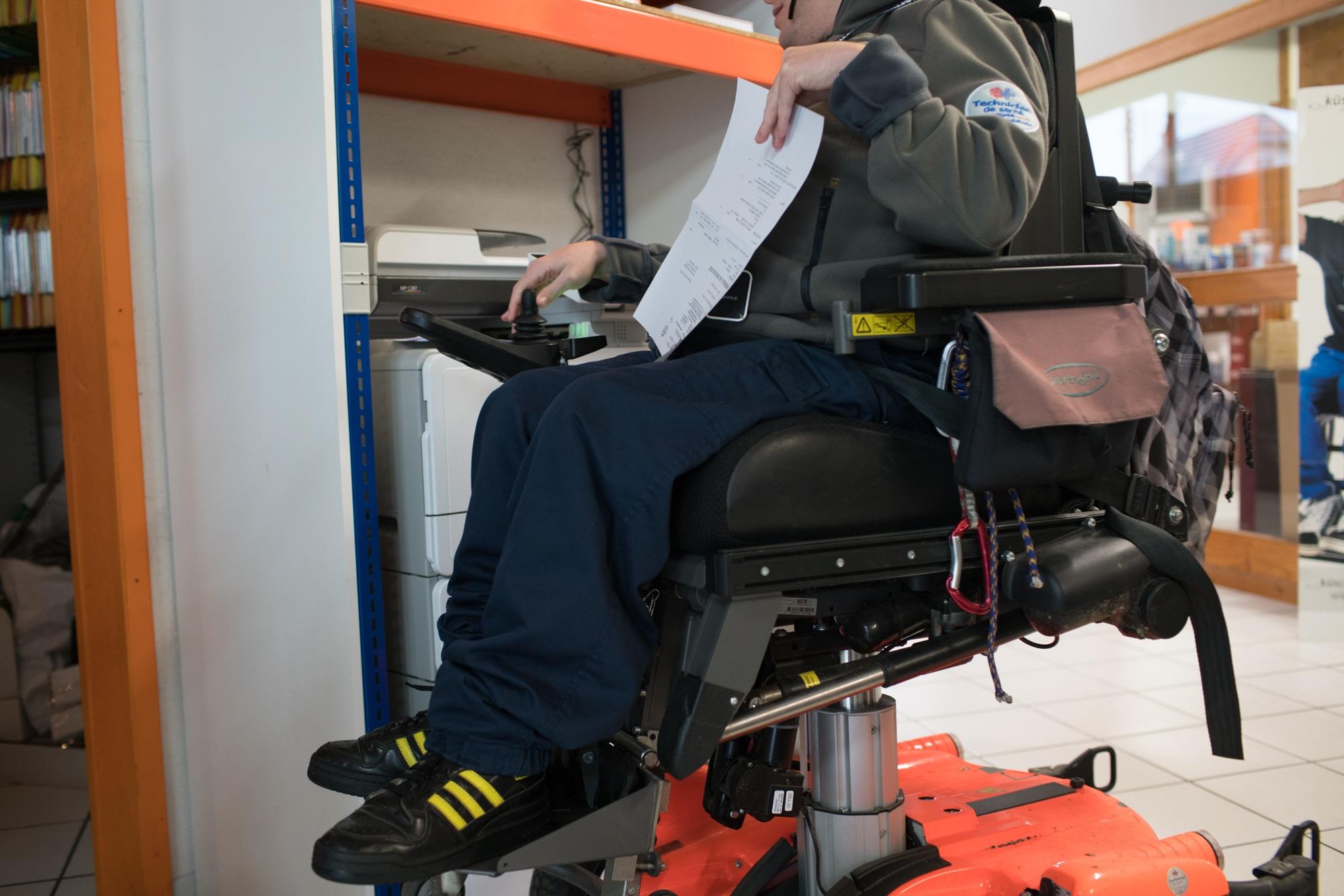 Edouard actionne son fauteuil, qui s'élève à la verticale pour lui permettre d'accéder à une étagère