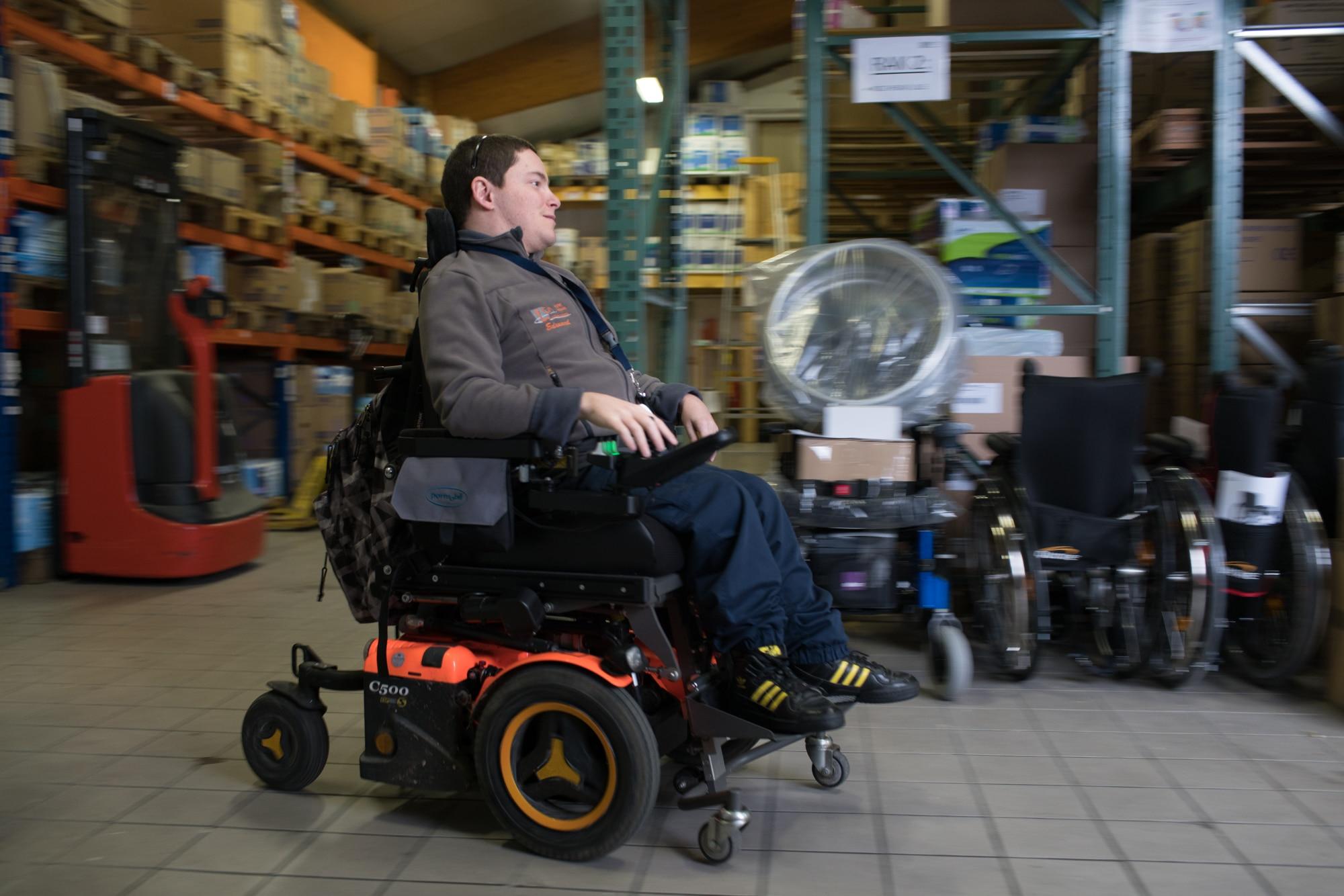 Edouard circule dans l'entrepôt sur son fauteuil