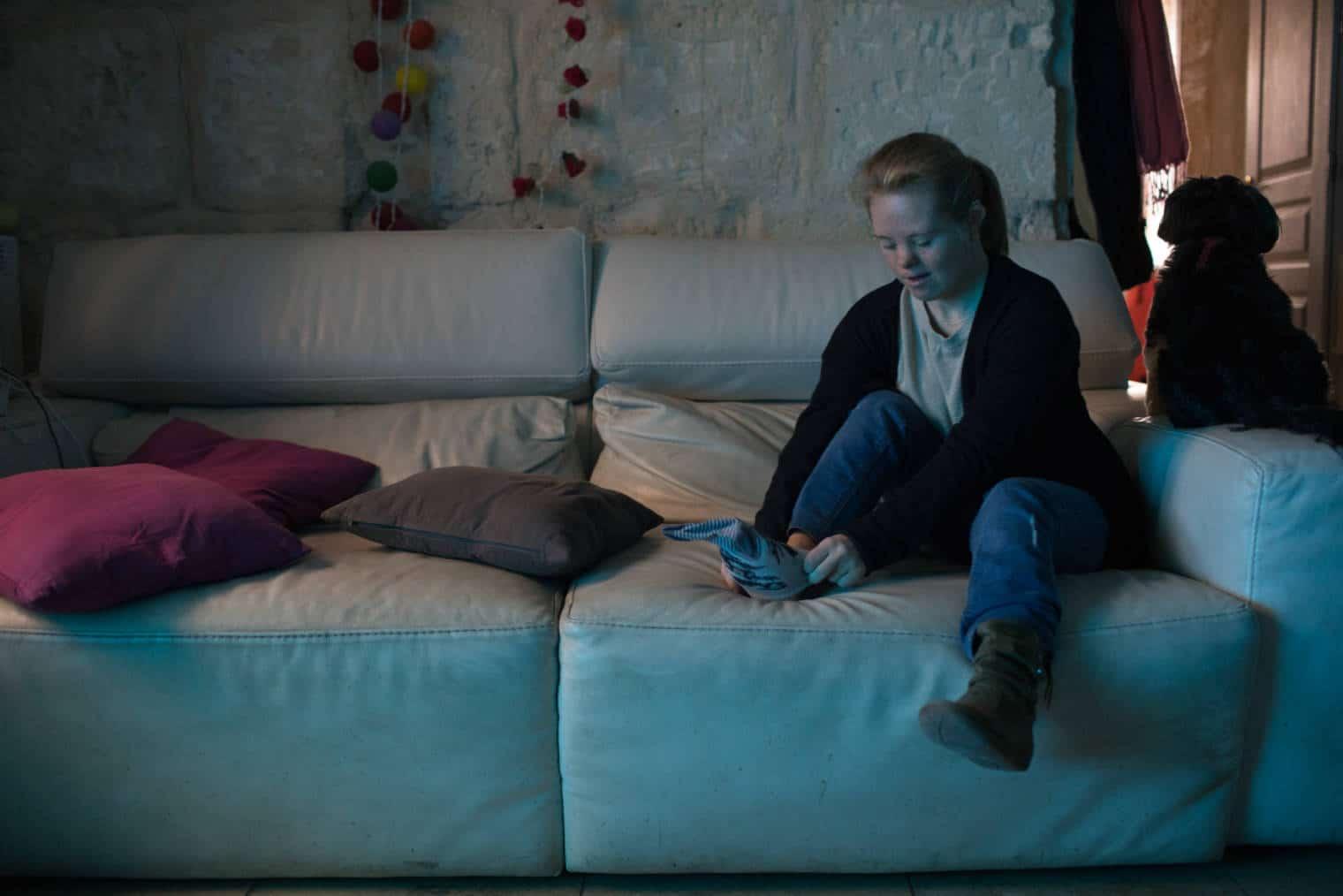 Émilie enfile une chaussette sur un canapé en cuir blanc chez elle, devant un mur en pierres